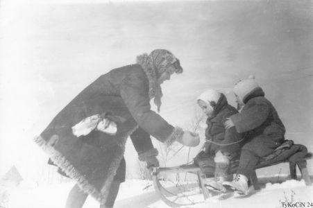 """zdjęcie zrobione na tykocińskich """"glinkach. Sądząc po posturze mojej i siostry przede mną siedzacej na sankach to będzie rok 1968. Ta młoda osoba w kożuchu to nasza Mama."""